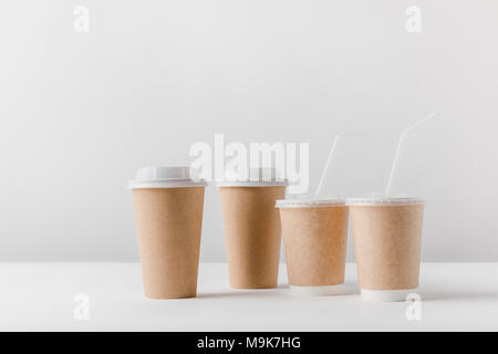 different coffee in paper cups on tabletop - Stock Photo