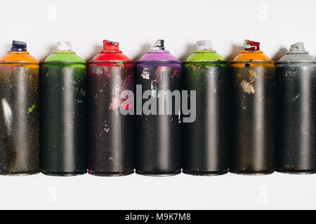 top view of arranged colorful spray paint in cans isolated on white - Stock Photo