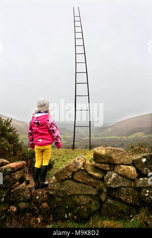 A young girl looks up at a gigantic ladder erected on Dartmoor National Park in Devon. The piece of public art measures approx 100ft in height. - Stock Photo