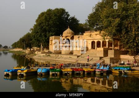Small colourful boats on Gadisar lake in front of Temple Gadi Sagar Jaisalmer Rajashan India - Stock Photo