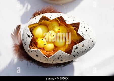 Cracked egg with cotton chickens. Easter decoration. - Stock Photo