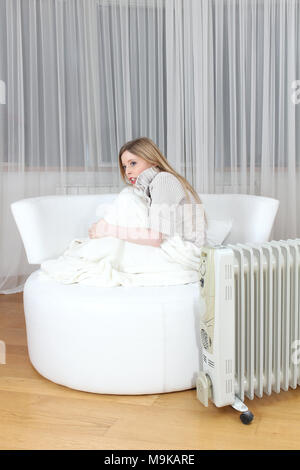 Young girl curled up on a chair next to radiator shivering with cold - Stock Photo