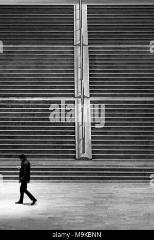 Man walking and looking at the smartphone - Stock Photo
