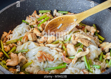 Asian noodles with arrows of garlic and pieces of meat are fried in a skillet according to a recipe for cooking homemade noodles - Stock Photo