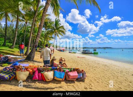 Trou-aux-Biches, Mauritius - Jan 4, 2017. Vendors on beach in Trou-aux-Biches, Mauritius. Trou-aux-Biches is a small town with a public beach on the n - Stock Photo