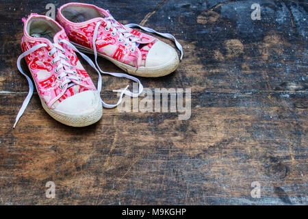 Pink and White Shoes With Love Shape Strap. Old Pink Shoes. Worn Out Pink White Shoes Flat lay on Old Blackboard. - Stock Photo