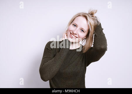 happy young woman smiling with hands in hair - Stock Photo