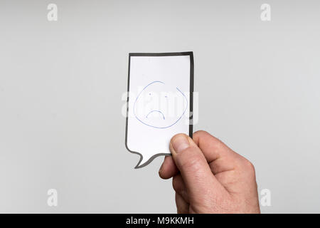 a white sheet with the drawing of a sad face - Stock Photo