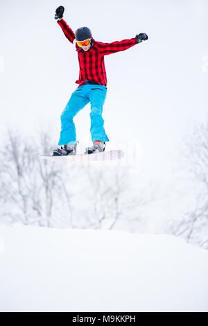 Picture of sportive man snowboarder jumping on snowy hill - Stock Photo