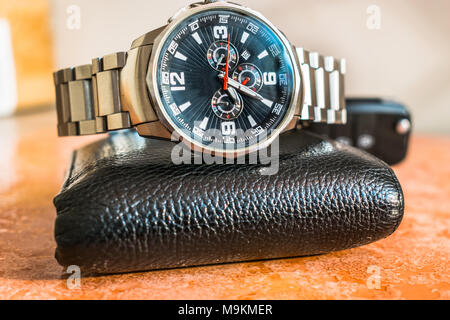 an expansive and stylish brand new set of a black shining leather wallet and a silver man's big dial watch kept on a marble brownish floor - Stock Photo