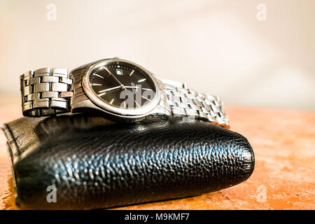 an expansive and stylish brand new set of a black shining leather wallet and a silver thin dial watch with a kept on a marble floor - Stock Photo