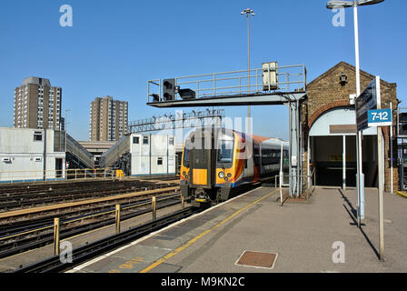 Train arriving into Clapham Junction station platform. - Stock Photo