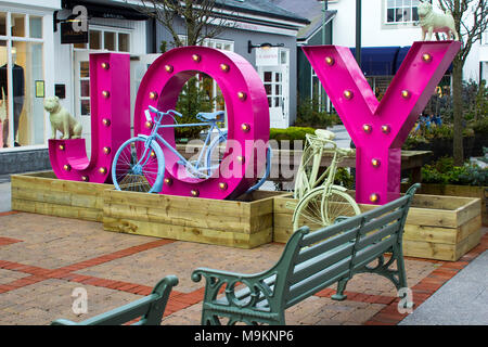 A large sign on a gable wall at the entrance to the prestigious Kildare Village retail park in County Kildare Ireland - Stock Photo