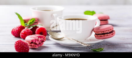 Cup of coffee with french raspberry macaroons - Stock Photo