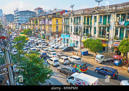 YANGON, MYANMAR - FEBRUARY 14, 2018: The daily traffic jam in  Anorata Road with a view on the old residential buildings, stretching along the street, - Stock Photo