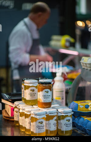 Jars of chicken stock and chicken gravy on sale at a butchers stall on borough market in central london. Products n sale at a delicatessen stall. - Stock Photo
