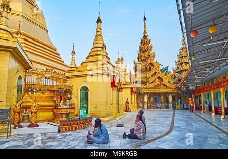 YANGON, MYANMAR - FEBRUARY 14, 2018: The Buddhist worshipers during the prayer in Sule Pagoda, on February 14 in Yangon. - Stock Photo