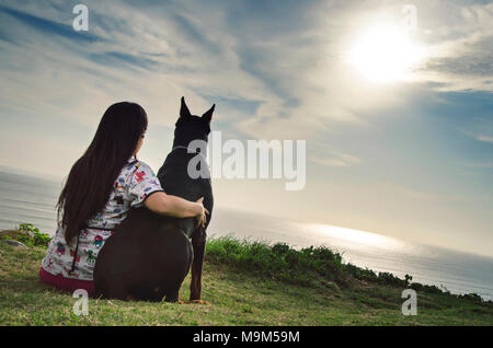 A woman and her dog watching the sunset - Stock Photo
