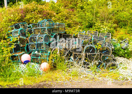 Abandoned and overgrown lobster pots or creels near the harbour at Tayvallich on Loch Sween, Argyll, Scotland - Stock Photo