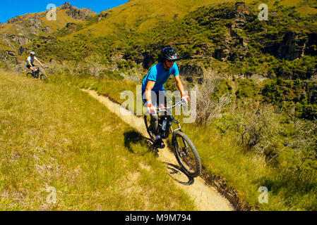 Mountain bikers descending the Pack Track in Skippers Canyon near Queenstown, New Zealand - Stock Photo