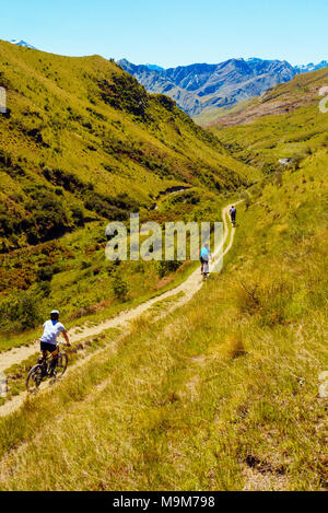 Mountain bikers descending the Pack Track in Skippers Canyon near Queenstown, New Zealand with Mt Aurum on the skyline - Stock Photo