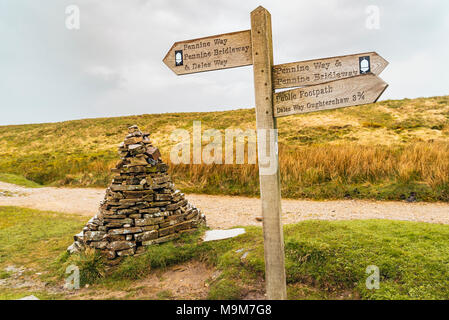 Direction sign and cairn at intersection of several walking and biking routes on the Cam High Road between Ribblesdale and Langstrothdale, Yorkshire - Stock Photo