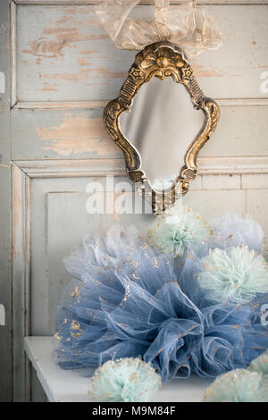 French mirror on wood panelling with tulle pom poms - Stock Photo