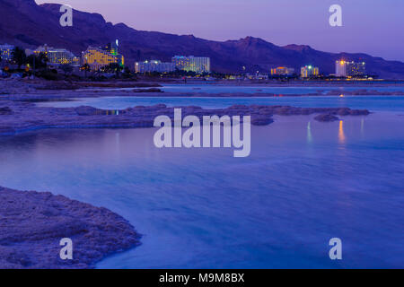 EIN BOKEK, ISRAEL - MARCH 16, 2018: Sunset view of salt formations in the Dead Sea, Ein Bokek resort, and visitors. Southern Israel - Stock Photo