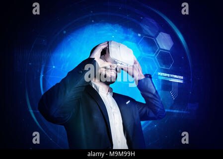 Cheerful young man smiling while putting on virtual reality glasses - Stock Photo