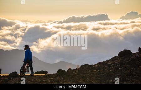 Mountain Biker on a Summit Above the Clouds in Early Morning Sunrise on Mounti Haleakala Hawaii