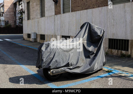 Covered scooter in an empty street - Stock Photo