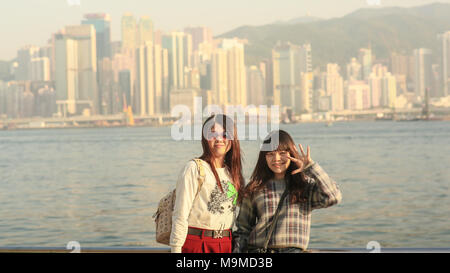 Hong Kong, China - January 1, 2016: Two young chinese tourist girls posing positively on the coast in Hong Kong, against a backdrop of a city panorama from Victoria harbor. - Stock Photo