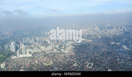 A view of the city of Manila through the window from the plane. Impressed photo of a tourist in flight over the capital. Philippines. - Stock Photo