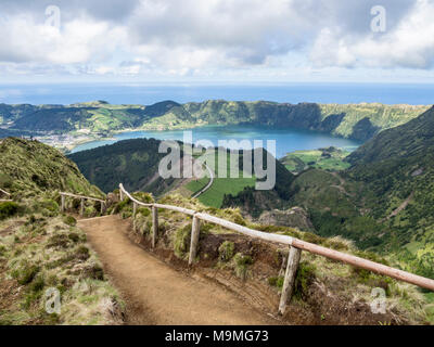 Path to the Road Below: A dirt path with wooden handrails winds over the hills to a spectacular viewpoint high over Sete Cidades and seems to connect to a road far below. - Stock Photo