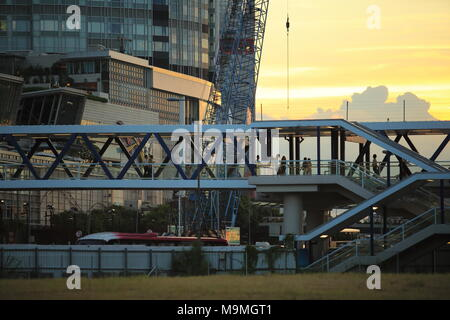 people pass through the busy footbridge to the ferry pier behind the IFC international finance center in Central, Hong Kong under the sunset - Stock Photo