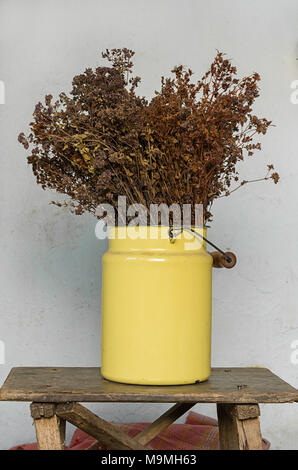House decoration concept: dried meadow flowers in a yellow metal pot on old wooden stool with nails sticking out - Stock Photo