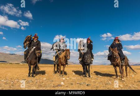 Mongolian eagle hunters on horses in the desert, Mongolia - Stock Photo