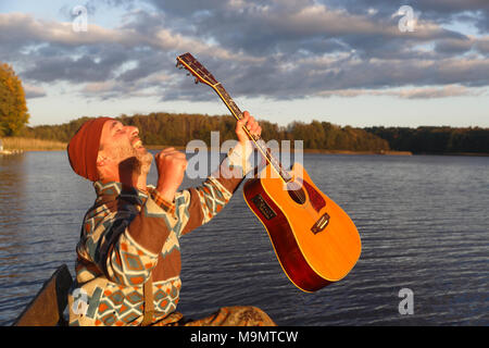 Man plays guitar on a boat landing stage at the lake and is pleased, Mecklenburg Lake District, Mecklenburg-Western Pomerania - Stock Photo