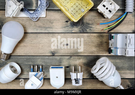 Close up of elements for residential electrical installation photographed on an aged wooden table. - Stock Photo