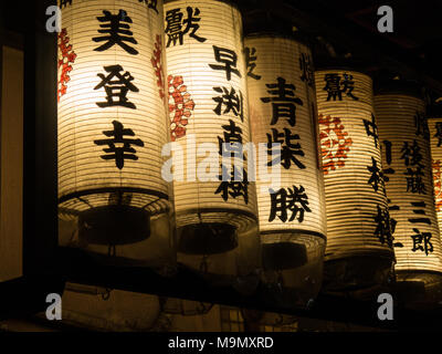 Illuminated lanterns in front of Tokyo restaurants. - Stock Photo