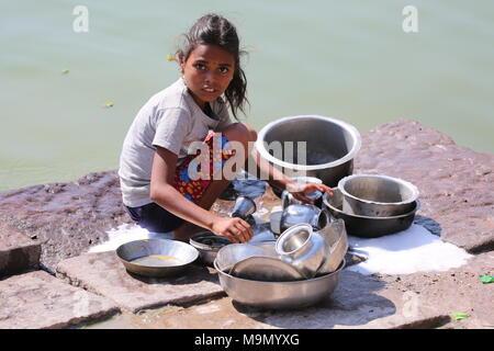 Indian girl washing dishes at the river -  indisches Mädchen beim Gechirr waschen am Fluss - Stock Photo