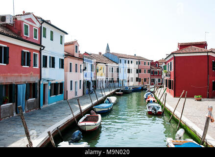 Colorful houses along a canal in Burano, Venice, Italy. Burano is a cozy island in Venetian Lagoon known for its colored homes. - Stock Photo