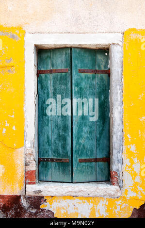 Old wooden window and yellow wall of a house in Burano island near Venice, Italy, Europe - Stock Photo