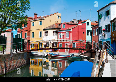 Brightly colorful houses reflected in the canal in Burano, a beautiful island in the Venetian lagoon near Venice, Italy, Europe - Stock Photo
