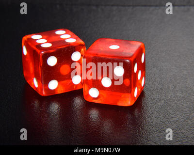 Red Casino Gambling Dice on Black Reflecting Background - Close Up - Stock Photo