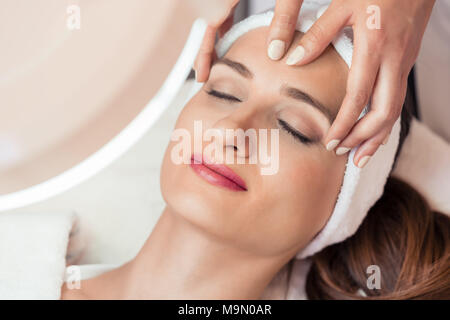 Relaxed woman smiling under the benefits of anti-aging facial massage - Stock Photo