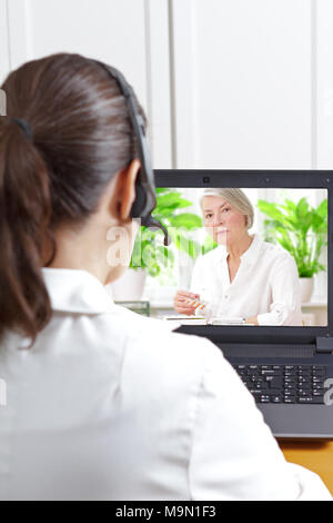 Female doctor of geriatrics with headset in front of her laptop during a video call with an old patient about her prescribed drugs, digital health - Stock Photo
