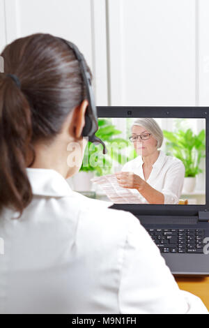 Pharmacist with headset in front of her laptop during a video call with an elderly patient holding the information sheet of her prescribed drugs - Stock Photo