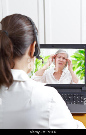 Female doctor with headset in front of her laptop during a video call with a fibromyalgia patient having sleeping trouble and headaches. - Stock Photo