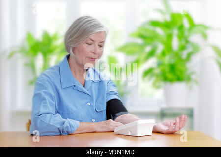 Senior woman suffering from hypertension sitting at a table in her living room measuring her blood pressure - Stock Photo